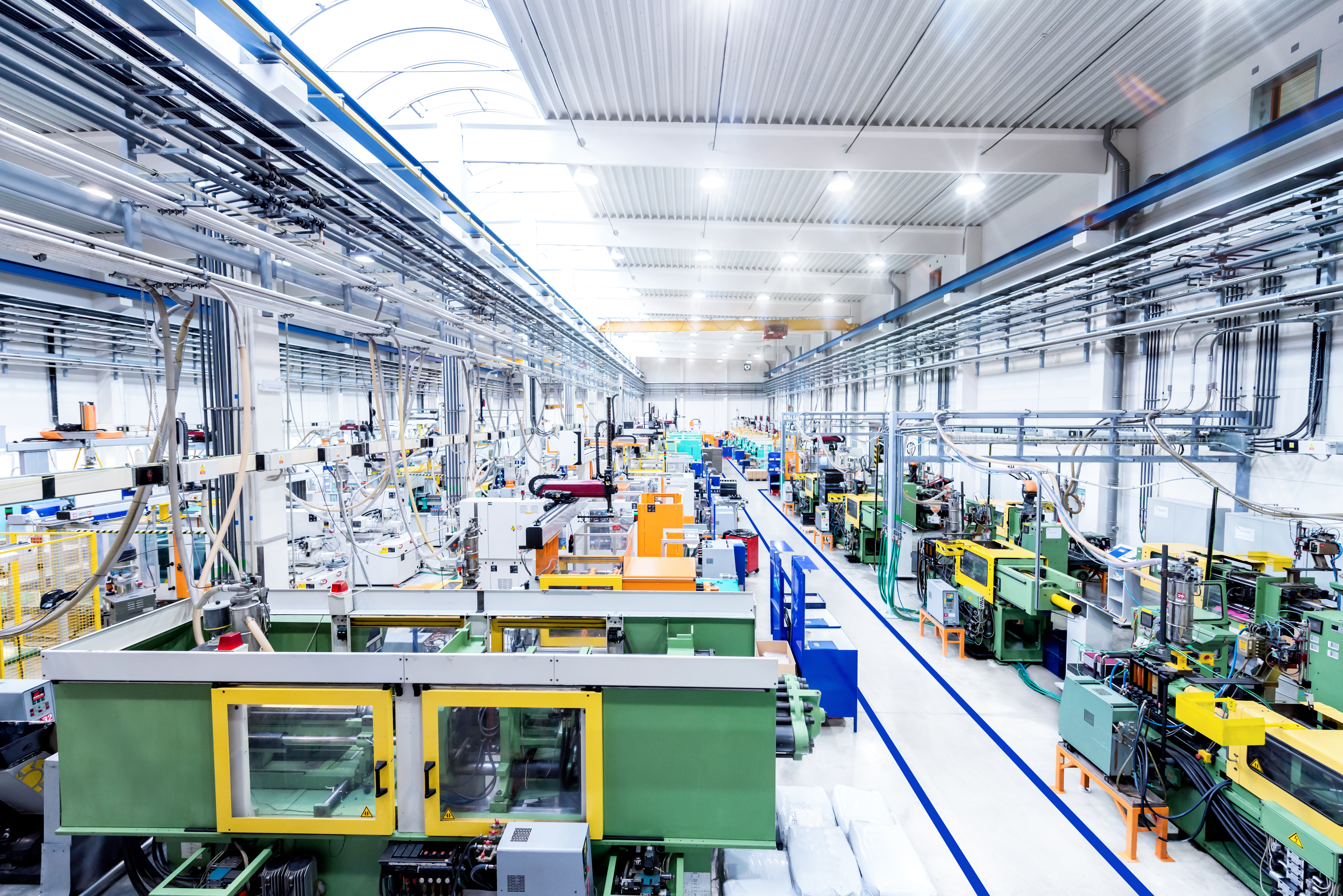 Horizontal color image of futuristic factory. Industrial aisle surrounded by modern machines which having busy robotic arms with molding shapes and producing plastic pieces for variety of industry. Labor intensive production line with manufacturing equipment.