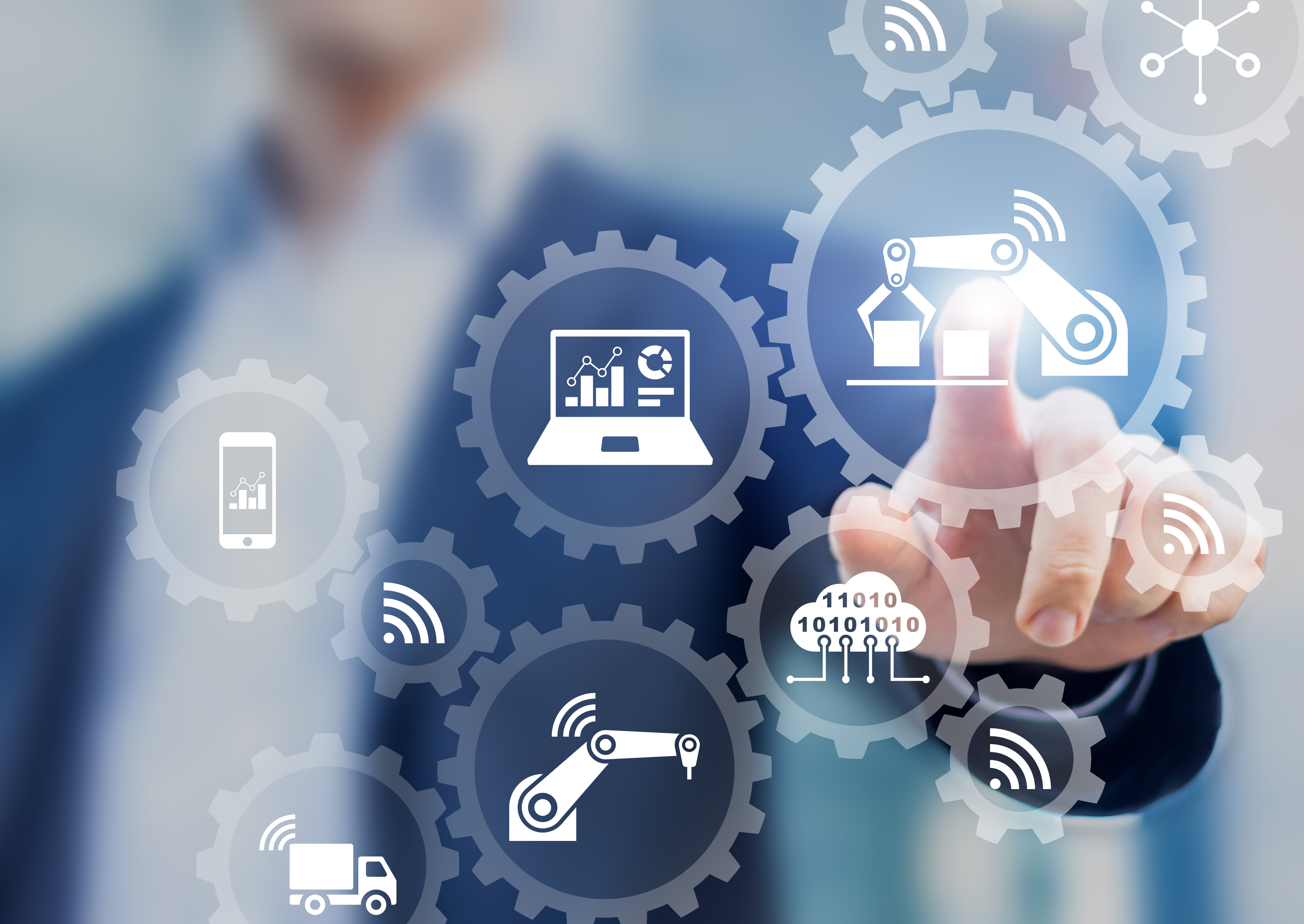 Smart factory and industry 4.0 concept with connected production robots exchanging data with internet of things (IoT) and cloud computing technology, businessman touching interface with icons in gears