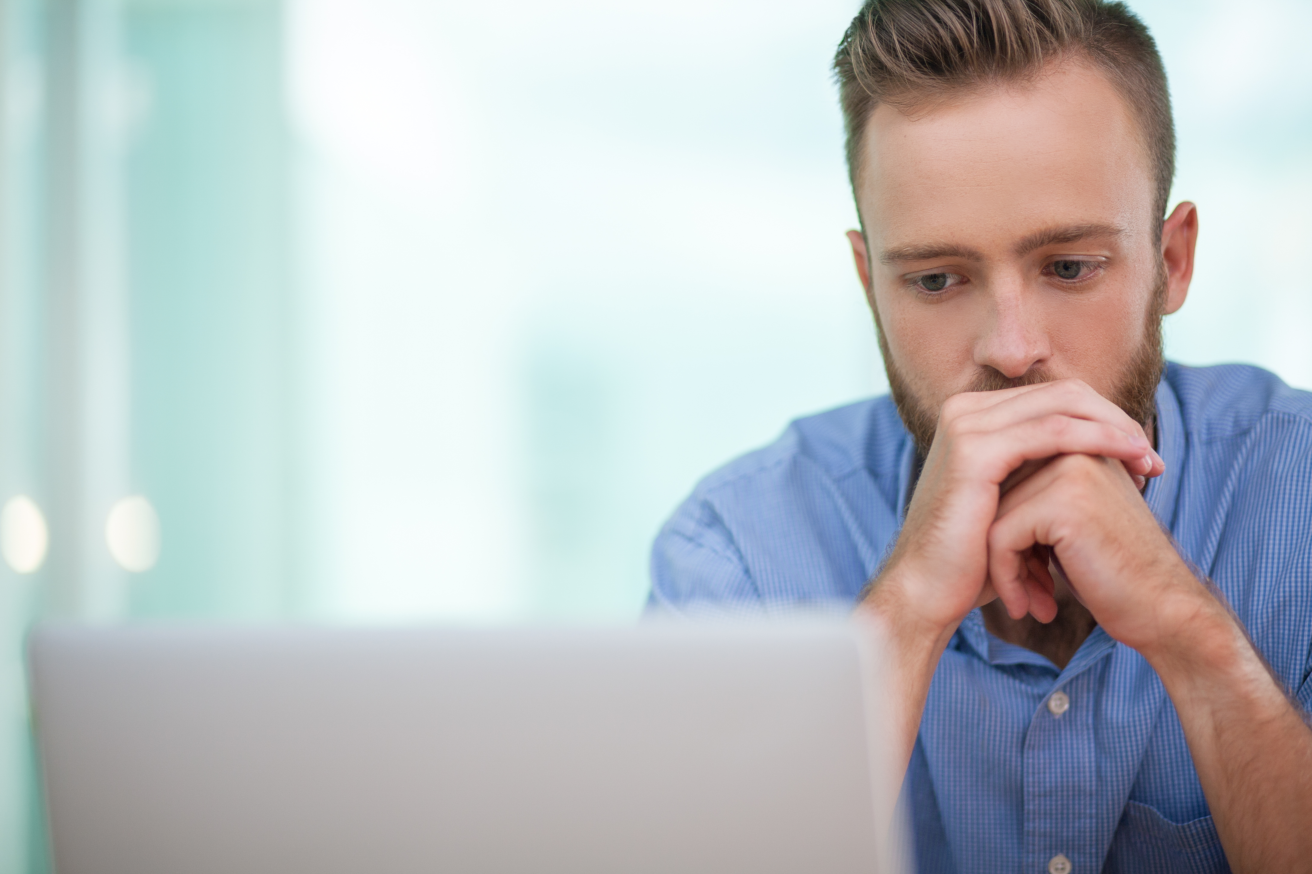 Serious bearded Caucasian businessman looking attentively at laptop screen and trying to solve complicated task