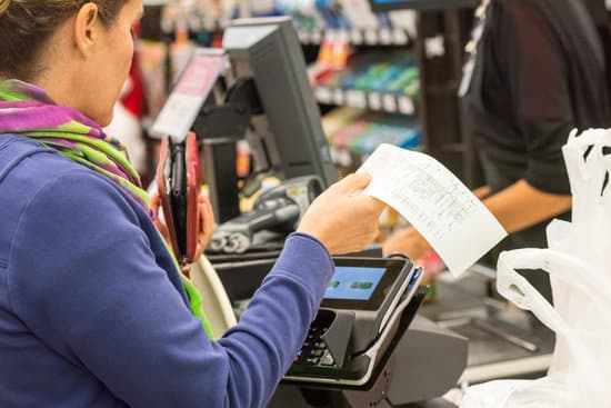 Caucasian woman electronic signing her bill at the supermarket